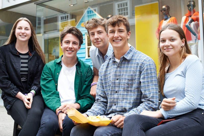 Porträt von den Jugendfreunden, die heraus in der zusammen essenden Stadt hängen lizenzfreie stockfotografie