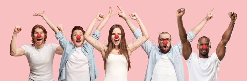 Porträt von den jungen Leuten, die roten Nasentag auf korallenrotem Hintergrund feiern stockbild