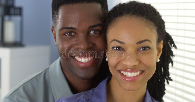 Porträt von den jungen Paaren, die Kamera betrachtend sich halten lizenzfreie stockfotografie