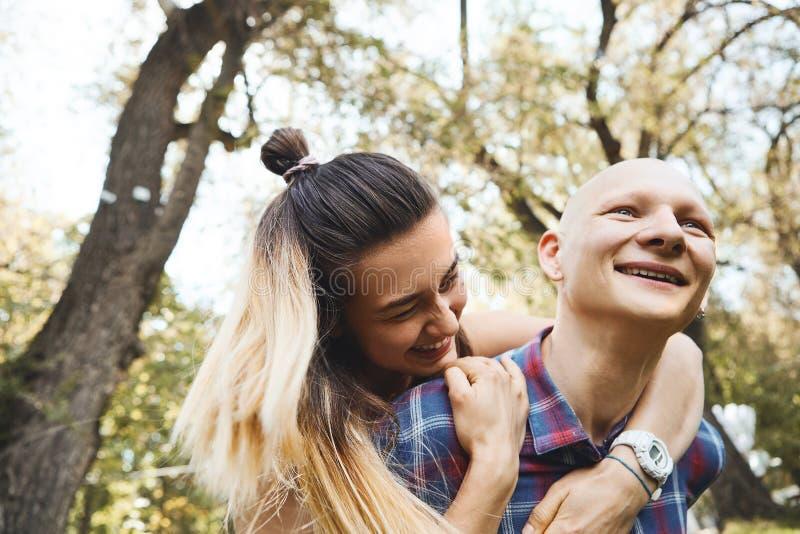 Porträt von den jungen Paaren, die Spaß haben und im Park lachen Freund, der seine Freundin auf Rückseite trägt lizenzfreies stockfoto