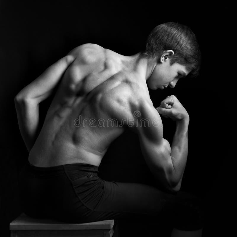 Porträt von den Jungen und von jugendlich Modell des Sitzes, die seine Muskeln im Studio aufwerfen lizenzfreies stockbild