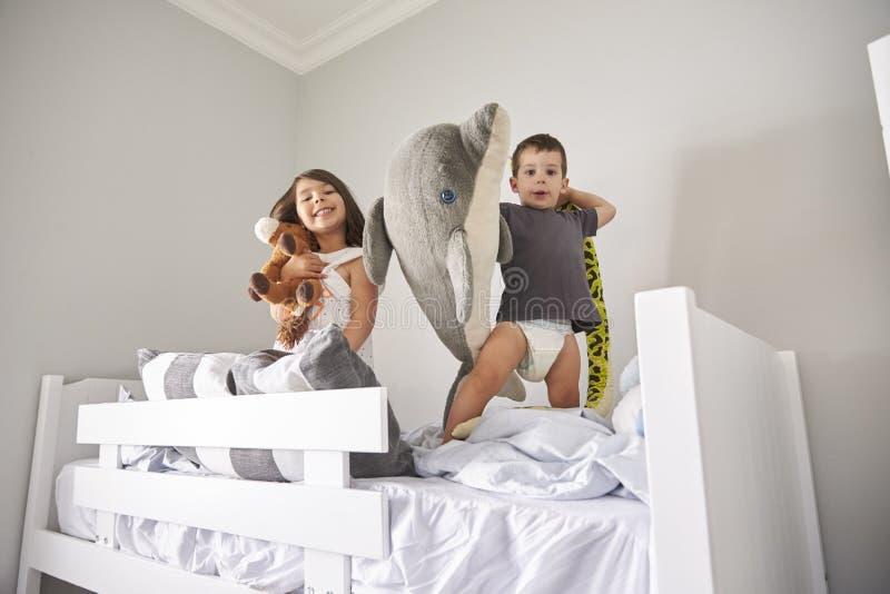 Porträt von den Kindern, die mit Spielwaren im Etagenbett spielen stockbilder