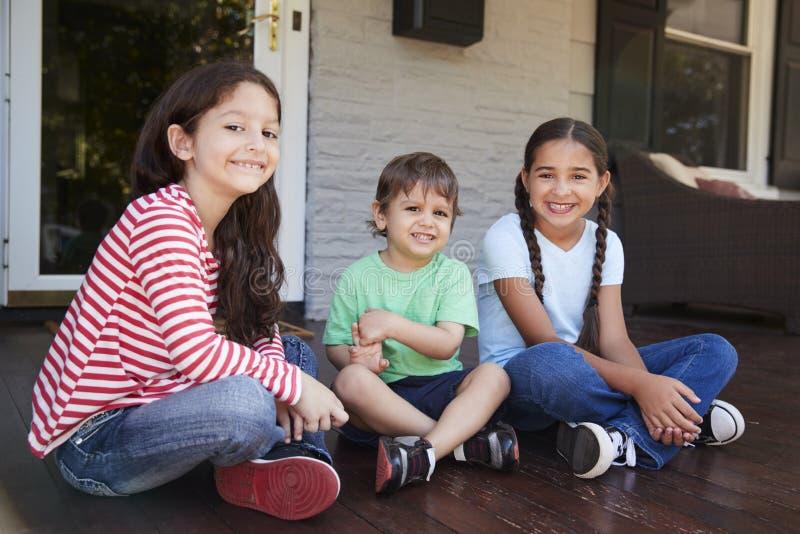 Porträt von den Kindern, die zusammen auf Portal des Hauses sitzen lizenzfreie stockfotografie