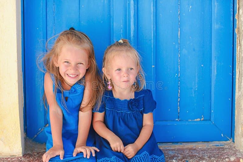 Porträt von den kleinen entzückenden Mädchen, die nahe altem sitzen stockbild