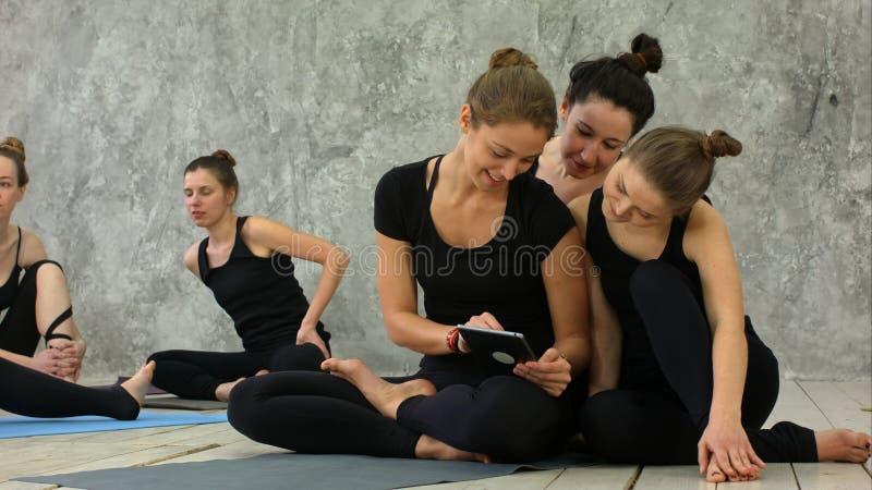 Porträt von den lächelnden geeigneten Frauen, die digitale Tablette beim Sitzen an der Yogamatte nach Eignungstraining verwenden stockbild