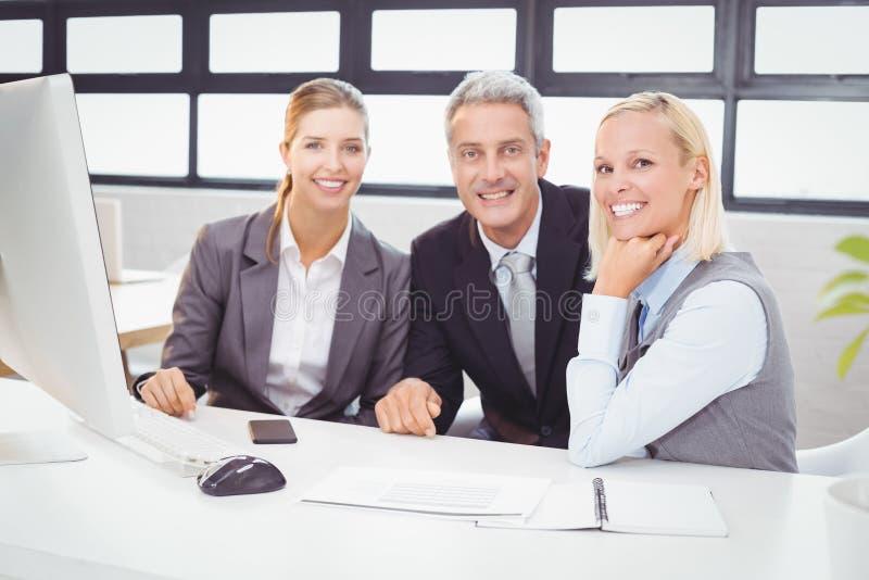 Porträt von den lächelnden Geschäftsfachleuten, die am Computertisch arbeiten lizenzfreie stockbilder