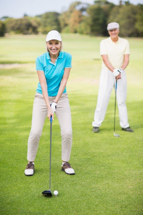 Porträt von den lächelnden reifen Paaren, die Golf spielen stockbild