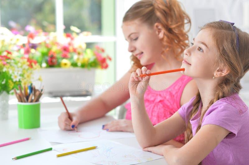 Porträt von den Mädchen, die zusammen bei Tisch zeichnen lizenzfreie stockfotos