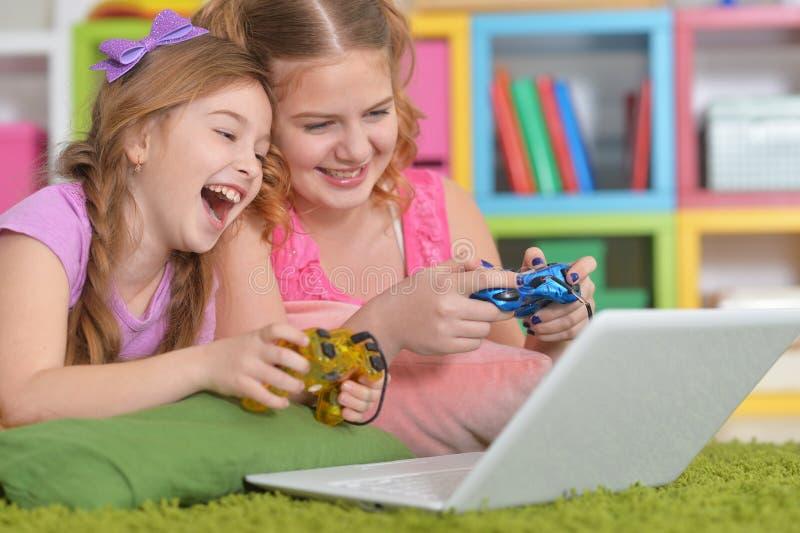 Portr?t von den M?dchen, die zusammen Computerspiel mit Laptop spielen stockbild