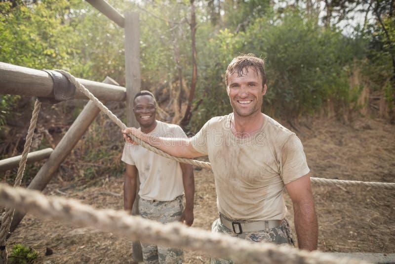 Porträt von den Militärsoldaten, die während des Hindernistrainings lächeln lizenzfreies stockfoto