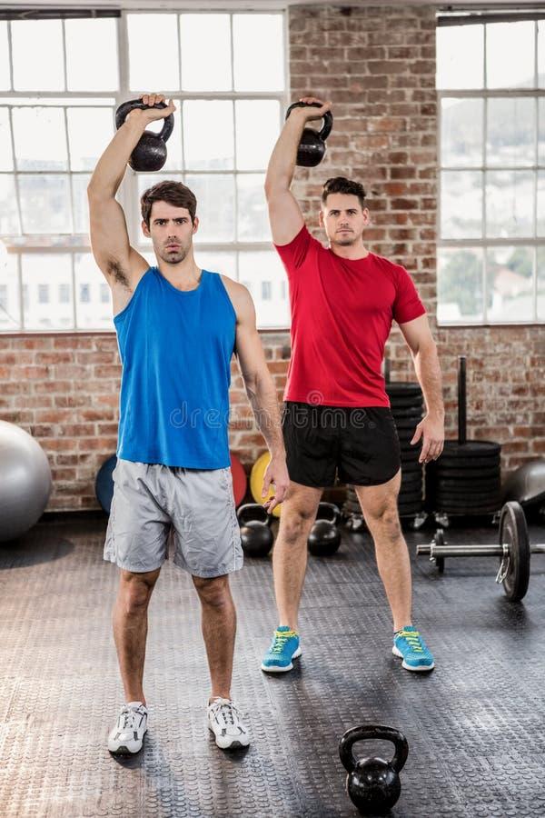 Porträt von den muskulösen Männern, die kettlebell anheben lizenzfreie stockfotos