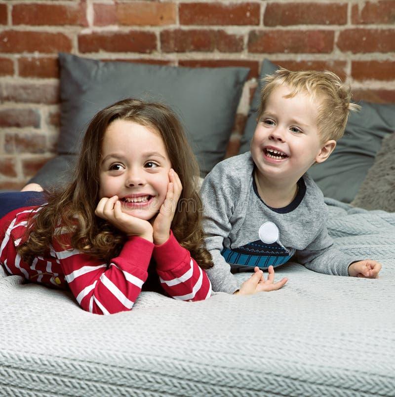 Porträt von den netten Geschwister, die im Schlafzimmer sich entspannen stockfoto