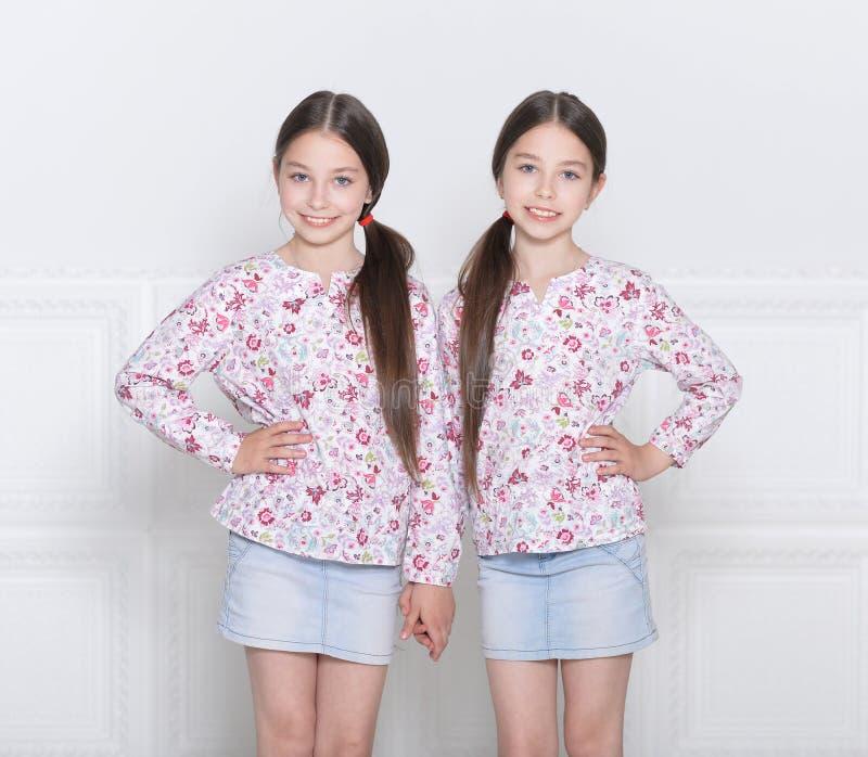 Porträt von den netten kleinen Mädchen, die auf weißem Hintergrund aufwerfen stockfotos