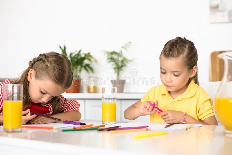 Porträt von den netten Kleinkindern, die bei Tisch Bilder zeichnen stockbilder