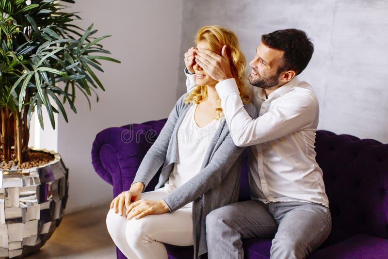 Porträt von den netten Paaren, die auf Sofa sitzen lizenzfreie stockbilder