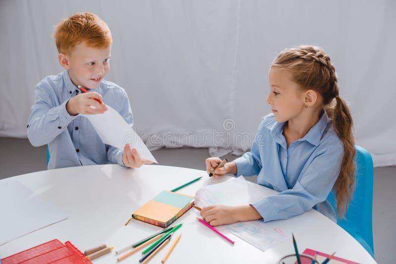 Porträt von den netten Vorschülern, die bei Tisch Bilder zeichnen lizenzfreie stockfotografie