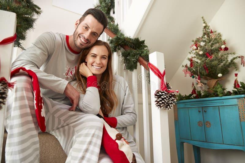 Porträt von den Paar-tragenden Pyjamas, die auf Treppe auf Weihnachtsmorgen sitzen lizenzfreie stockfotografie