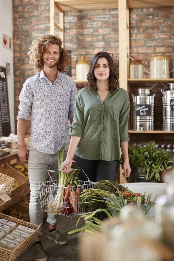 Porträt von den Paaren, die frisches Obst und Gemüse im stützbaren freien PlastikGemischtwarenladen kaufen lizenzfreie stockfotos