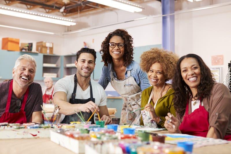 Porträt von den reifen Erwachsenen, die an Art Class In Community Centre mit Lehrer teilnehmen stockfotografie