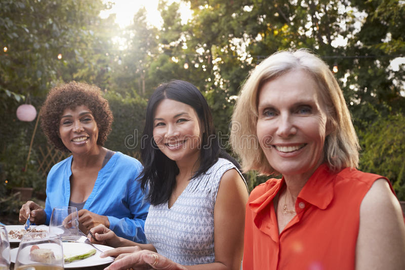Porträt von den reifen Freundinnen, die Mahlzeit im Freien genießen lizenzfreies stockbild