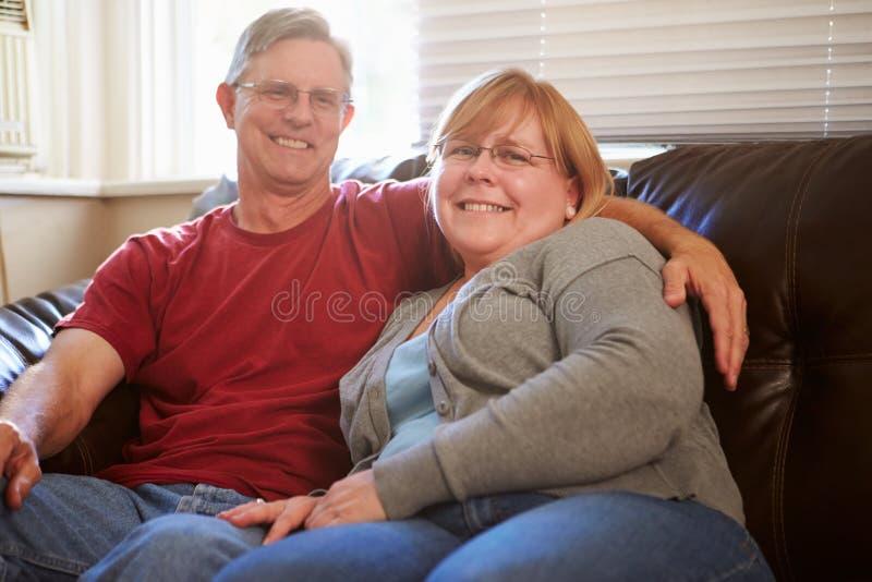 Porträt von den reifen Paaren, die auf Sofa At Home sitzen stockfotos