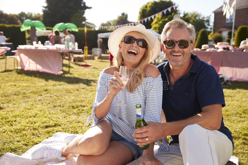 Porträt von den reifen Paaren, die auf Wolldecke an der Sommer-Garten-Party mit Getränken sitzen lizenzfreies stockbild