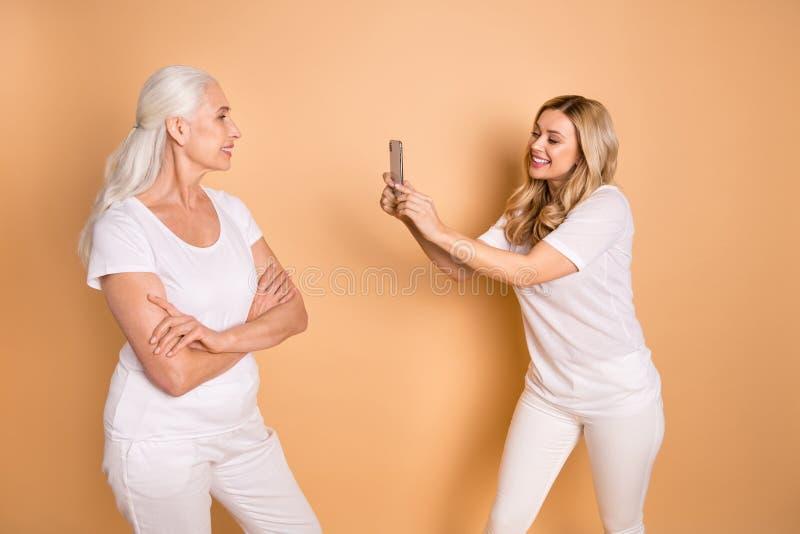 Porträt von den schön aussehenden reizenden attraktiven reizend netten netten heitren Damen, die das weiße T-Shirt Ausstattungsne stockbild