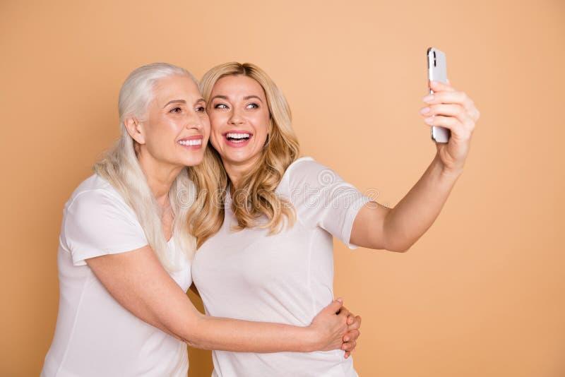 Porträt von den schön aussehenden reizenden süßen attraktiven reizend netten netten heitren Damen, die weißes T-Shirt Nehmen trag stockfoto