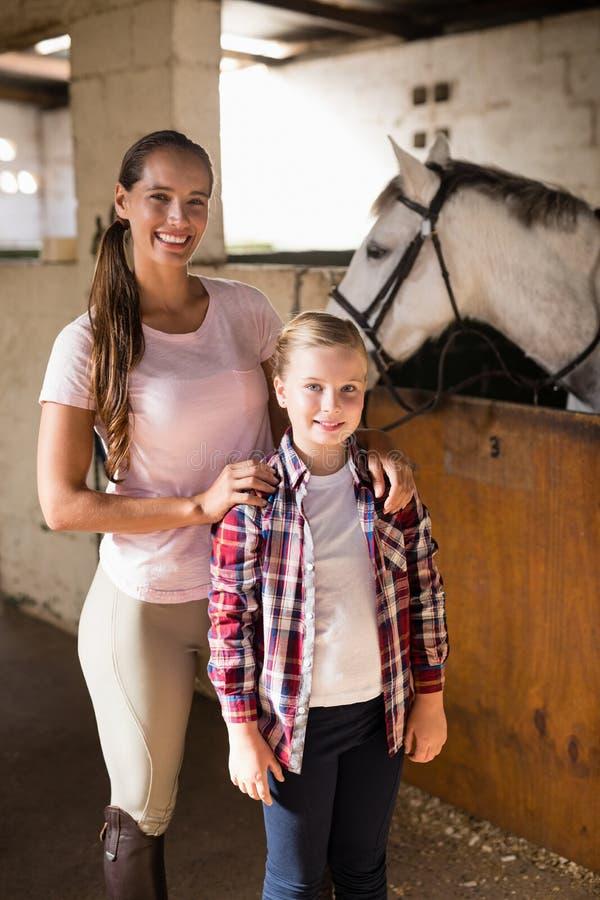 Porträt von den Schwestern, die Pferd bereitstehen stockbild
