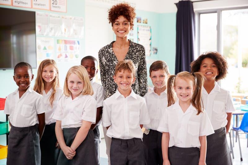Porträt von den Volksschule-Schülern, die einheitliche Stellung im Klassenzimmer mit weiblichem Lehrer tragen stockfotografie