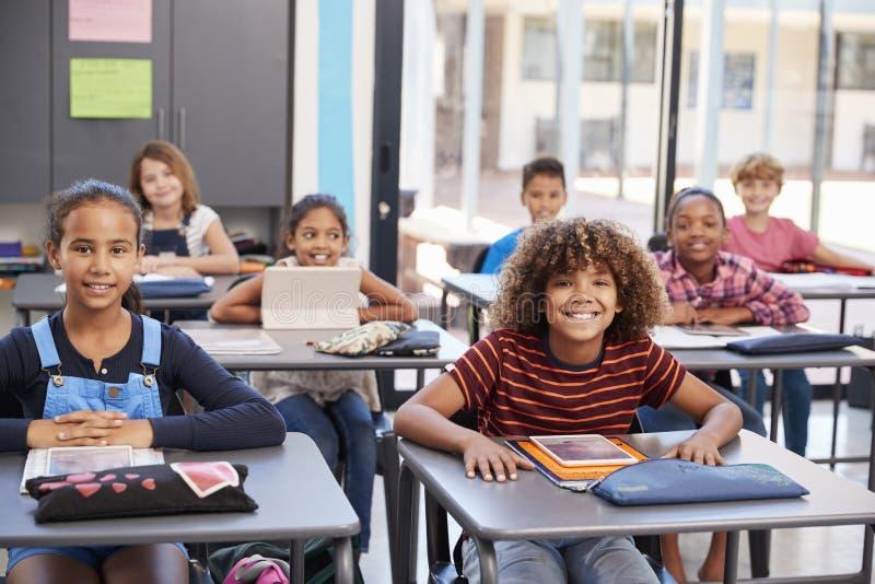 Porträt von den Volksschuleschülern, die an ihren Schreibtischen sitzen stockfotografie