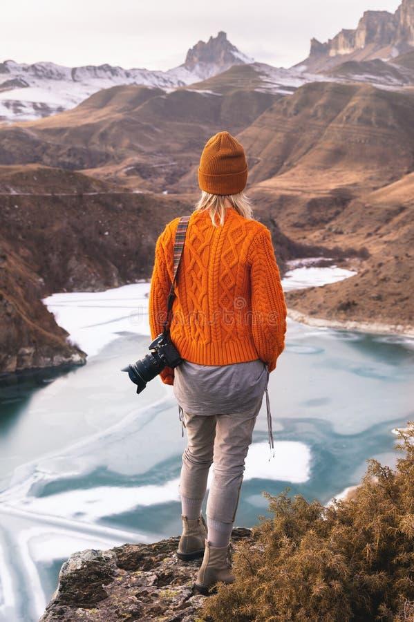 Porträt von der Rückseite des Mädchenreisendphotographen in einer orange Strickjacke und in einem Hut mit einer Kamera in der Han stockbilder