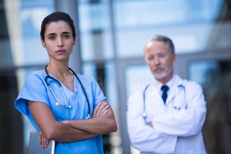 Porträt von Doktor und von Krankenschwester, die mit den Armen gekreuzt steht lizenzfreie stockfotografie
