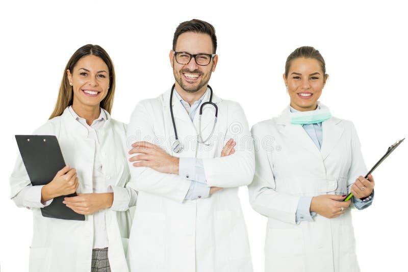 Porträt von drei glücklichen Doktoren, die und Lächeln stehen stockbild