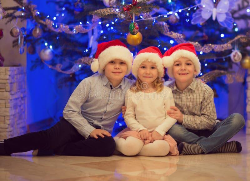 Porträt von drei glücklichen Kindern, die Spaß am Weihnachtsabend haben lizenzfreies stockfoto