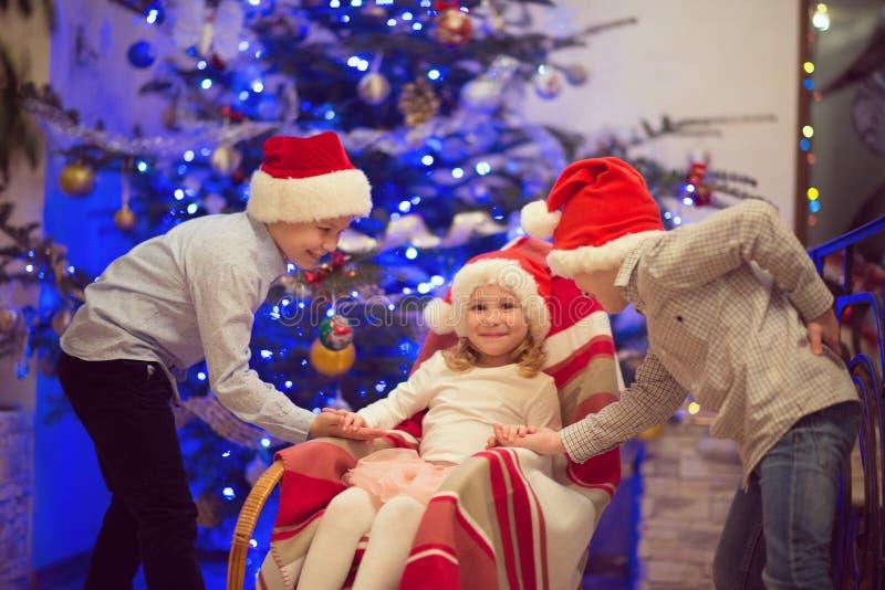 Porträt von drei glücklichen Kindern, die Spaß am Weihnachtsabend haben lizenzfreie stockfotos