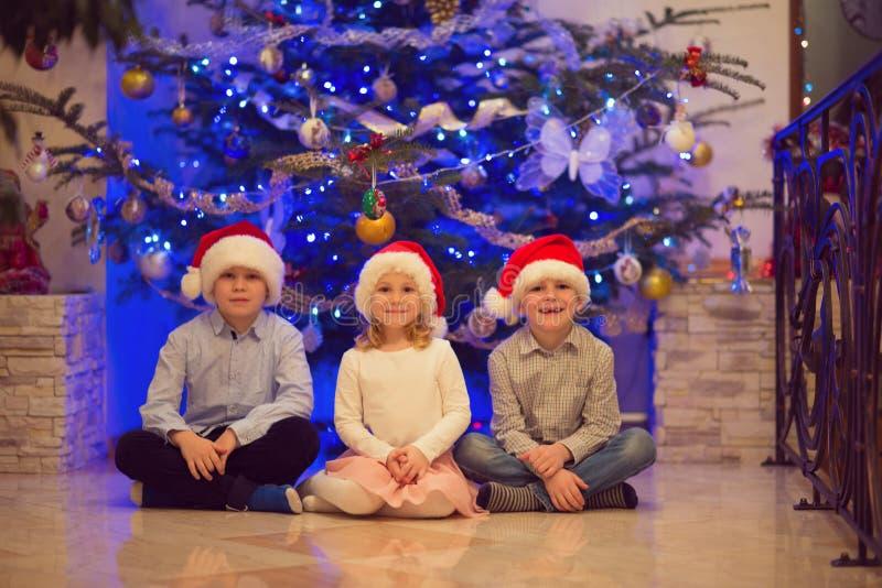 Porträt von drei glücklichen Kindern, die Spaß am Weihnachtsabend haben lizenzfreie stockbilder