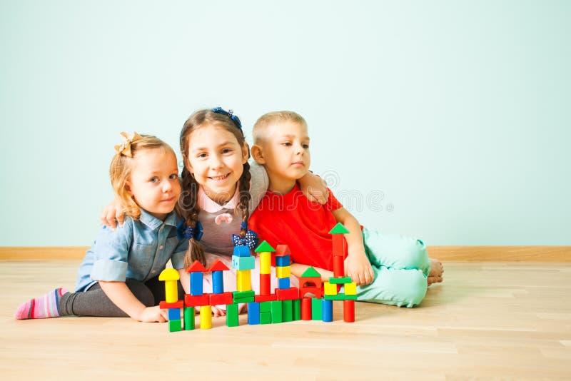 Porträt von drei Kindern auf einem Boden lächelnd zur Kamera lizenzfreies stockbild