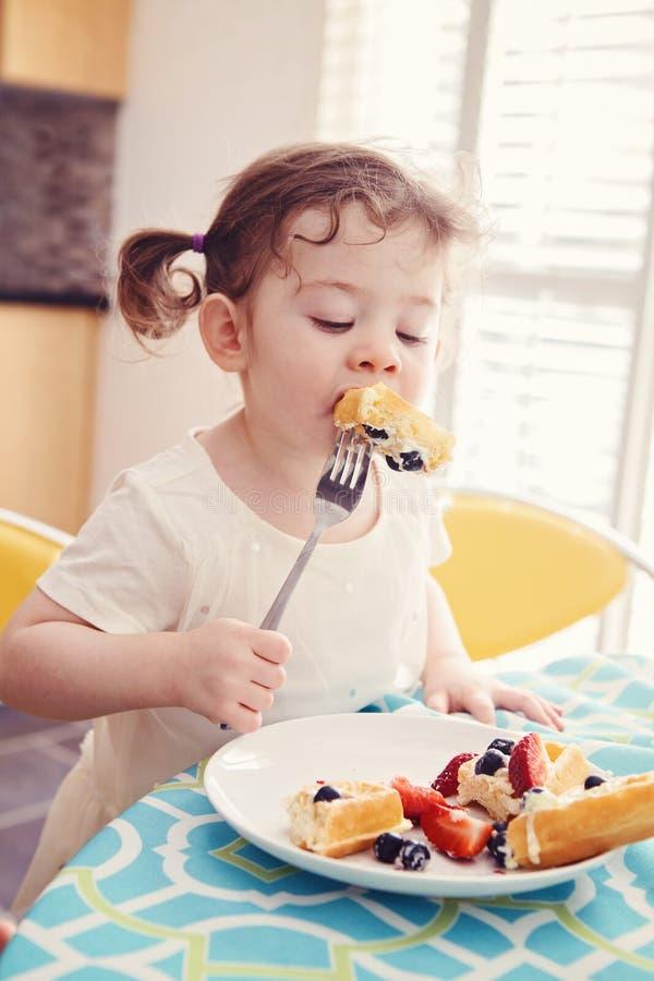Porträt von einem glücklichen weißen kaukasischen Kindermädchenkleinkind mit Zöpfen im weißen Kleid Frühstück essend waffles Früc lizenzfreie stockfotografie