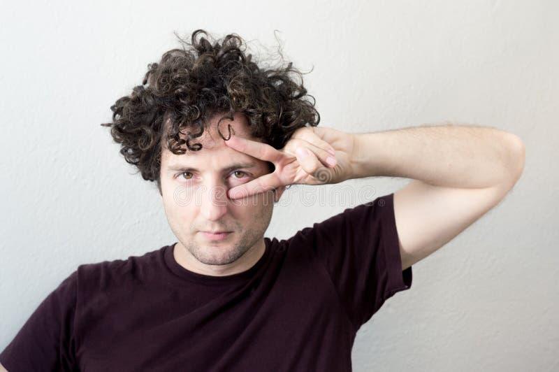 Porträt von einem jungen, kaukasisch, Brünette, gelocktes behaartes Mann gesturi stockbilder