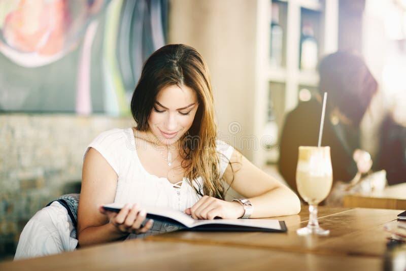 Porträt von einem jungen, von Schönheit, die allein in einem Café, Lesung, schauend interessiert und sitzt unterhalten stockfotografie