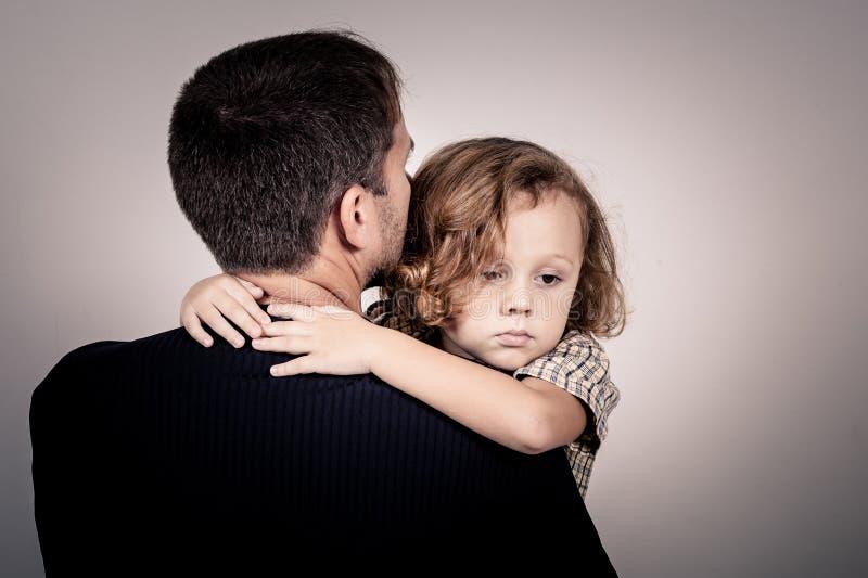 Porträt von einem traurigen Sohn, der seinen Vater umarmt stockbild