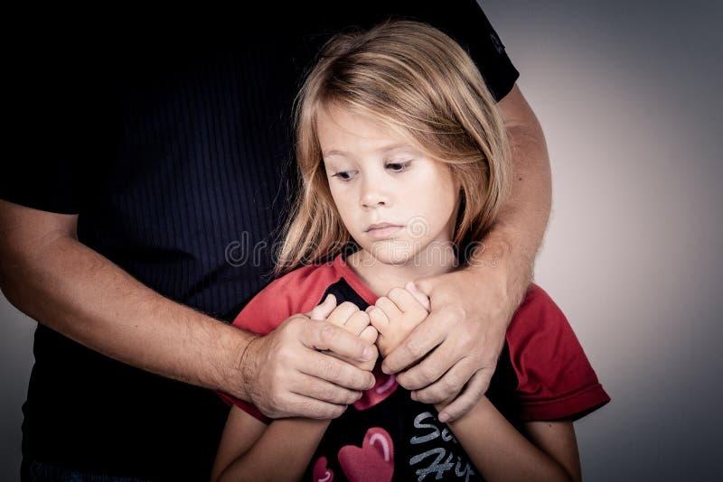 Porträt von einer traurigen Tochter, die ihren Vater umarmt stockfotografie