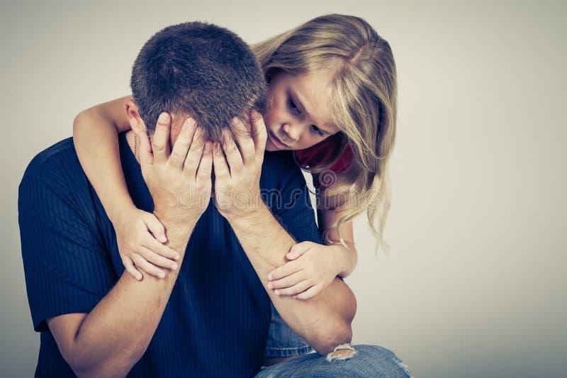 Porträt von einer traurigen Tochter, die ihren Vater umarmt lizenzfreie stockfotos