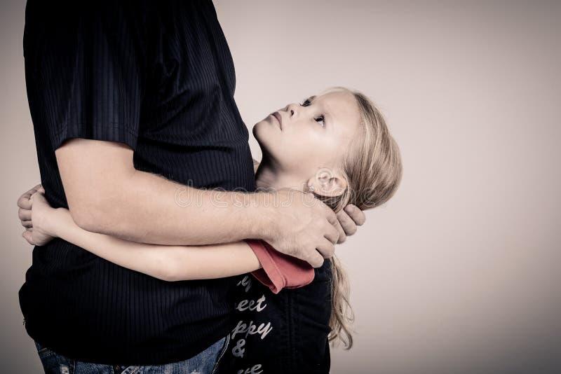 Porträt von einer traurigen Tochter, die ihren Vater umarmt stockfoto