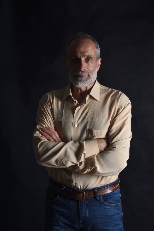 Porträt von ernsten mittleren gealterten Mannarmen kreuzte auf Weiß stockfotografie