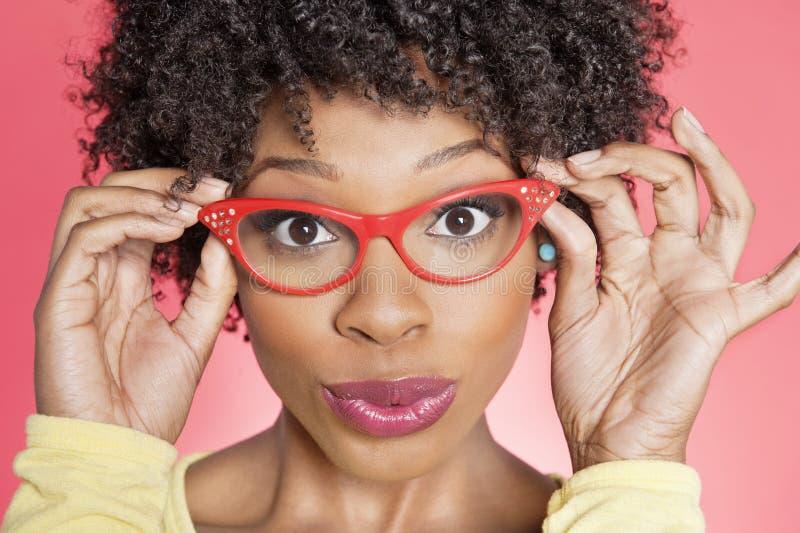 Porträt von Gläsern eines tragenden Retrostils der Afroamerikanerfrau über farbigem Hintergrund stockfoto