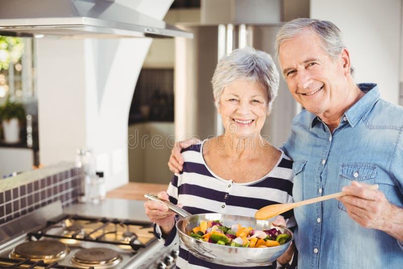 Porträt von glücklichen älteren Paaren mit dem Kochen der Wanne stockfotografie