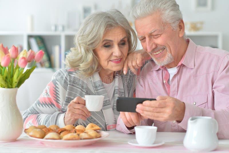 Porträt von glücklichen älteren Paaren mit trinkendem Tee des Smartphone lizenzfreies stockfoto
