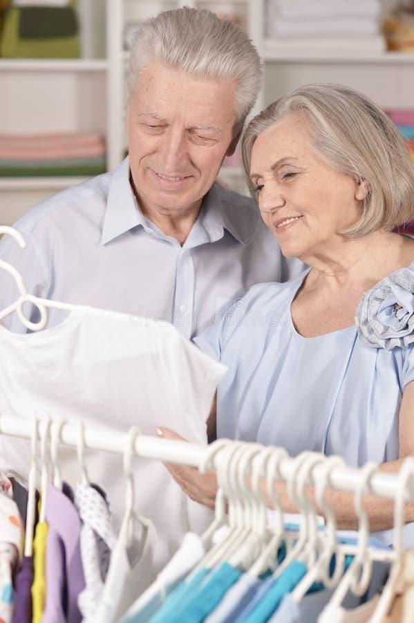 Porträt von glücklichen älteren Paaren nahe Gestell mit Hemden lizenzfreies stockfoto